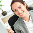 Bright hispanic businesswoman holding a light bulb sitting at he - Stock Photo