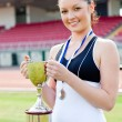 Joyful female athlete holding a trophy — Stock Photo