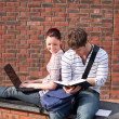 Two students working together with book and laptop outside — 图库照片