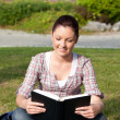 Relaxed female student reading a book sitting on grass — Stock Photo #10836408