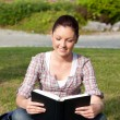 Relaxed female student reading a book sitting on grass — Stock Photo