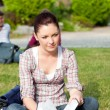 Thoughtful female student reading a book sitting on grass — Stock Photo #10836415
