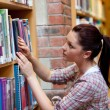 Pretty young woman looking for a book — Stock Photo