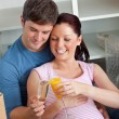 Joyful couple expecting a baby drinking and sitting on the floor — Stock Photo #10836515