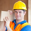 Young male worker carrying a wooden board — Stock Photo