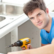 Handsome man holding a drill repairing a kitchen sink — Stock Photo