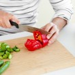 Close-up of a young man cutting vegetables in the kitchen — Stock Photo #10836560