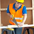 Handsome male worker wearing a yellow hardhat sawing a wooden bo — Stock Photo #10836564