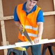 Charismatic male worker wearing a yellow hardhat sawing a wooden — Stock Photo #10836568