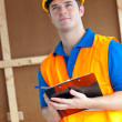 Thoughtful male worker holding a clipboard — Stock Photo #10836573