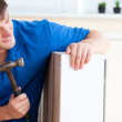 Young man building furniture using a hammer and a nail — Stock Photo #10836597