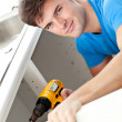 Charismatic man repairing his sink and holding a drill in the ki — Stockfoto