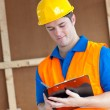 Handsome worker with hardhat taking notes on his clipboard — Stock Photo