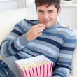 Handsome young man eating popcorn lying on the sofa — Stock Photo