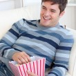 Cheerful young man eating popcorn lying on the sofa — Stock Photo
