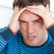 Caucasian man having a headache in the living-room - Stock Photo