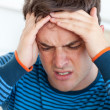 Handsome mhaving headache in living-room — Stock Photo #10836698