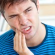 Unhappy caucasian man having a toothache in the living-room - Stock Photo