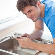 Assertive man repairing his sink in the kitchen — Stock Photo #10836747
