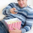 Relaxed young man eating popcorn and holding a remote lying on t — Stock Photo