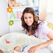 Attentive young mother taking care of her adorable baby — Stock Photo #10836785