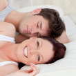 Smiling caucasian couple lying on bed — Stock Photo