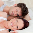 Positive caucasian couple lying on bed — Stock Photo