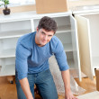 Cute man rolling a carpet out — Stock Photo #10837052