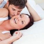 Veselá Kavkazský pár ležící na posteli — Stock fotografie