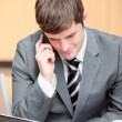 Concentrated businessman using his laptop while talking on phone — Stock Photo