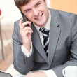 Charismatic businessman using his laptop while talking on phone — Stock Photo