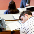 Asleep male student during an university lesson — Stock Photo