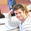 Delighted male student smiling at the camera during an universit — Stock Photo