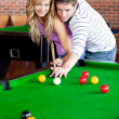 Affectionate boyfriend learning his girlfriend how to play pool — Stock Photo