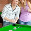 Caucasian couple playing cards on a billiard — Stock Photo #10837323