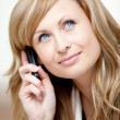 Thoughtful businesswoman talking on phone in her office — Stock Photo #10837364