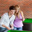 Cheerful couple playing cards on a billiard — Stock Photo #10837390