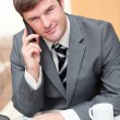 Confident businessman talking on phone and using his laptop — Stock Photo
