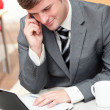 Assertive businessman talking on phone and using his laptop — Stock Photo