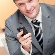 Elegant businessman writing a text message with his mobile phone — Stock Photo #10837397