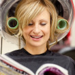 Happy woman reading a magazine with hair curlers under a hairdry — Stock Photo