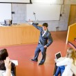 Confident teacher giving a lesson to university students — Stock Photo
