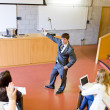 Confident teacher giving a lesson to university students - Stock Photo