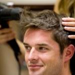 Female hairdresser drying her male customer's hair — Stockfoto