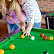 Affectionate boyfriend learning his girlfriend how to play pool — Stock Photo #10837488