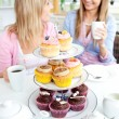 Stock Photo: Two cute friends eating cupcakes sitting in kitchen at home