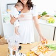 Smiling mother holding her sleeping child while preparing carrot — Stock Photo