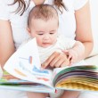 Happy mother showing a book to her baby sitting in the sofa at h — Stock Photo