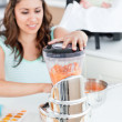 Beautiful mother mixing carrot with a blender for her baby lunch — Stock Photo