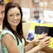 Adorable couple looking for a business book in a library — Stock Photo